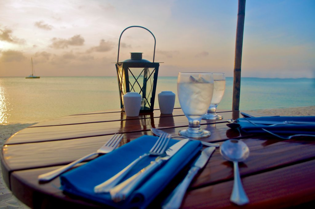 Table setting on the beach during sunset.