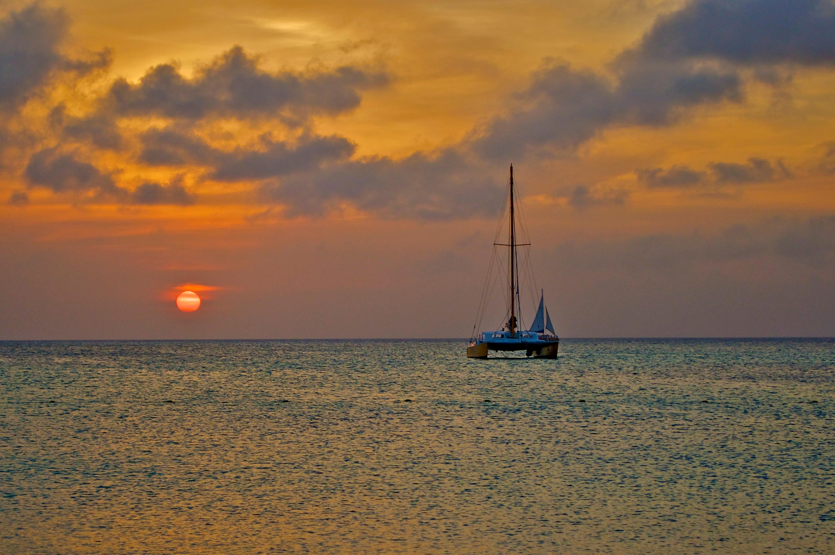 Catamaran on the ocean during sunset.