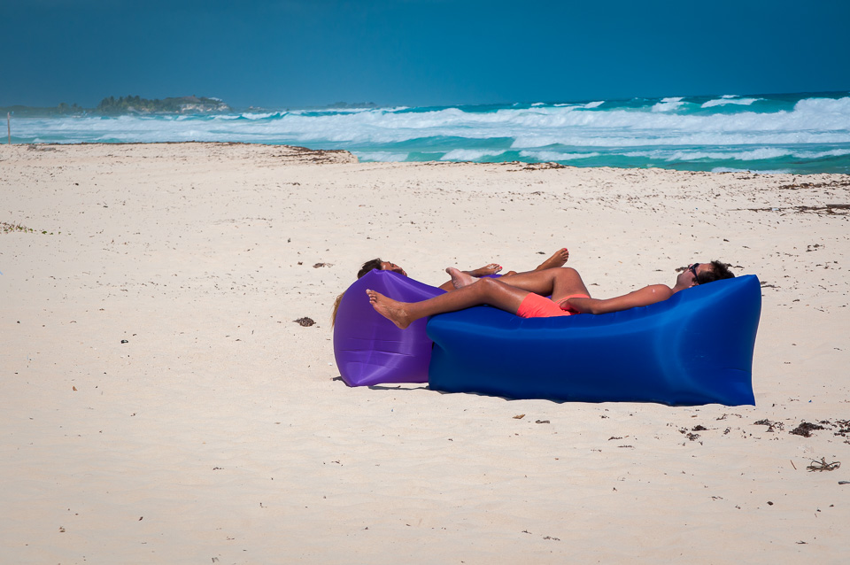A couple taking a nap on the beach.