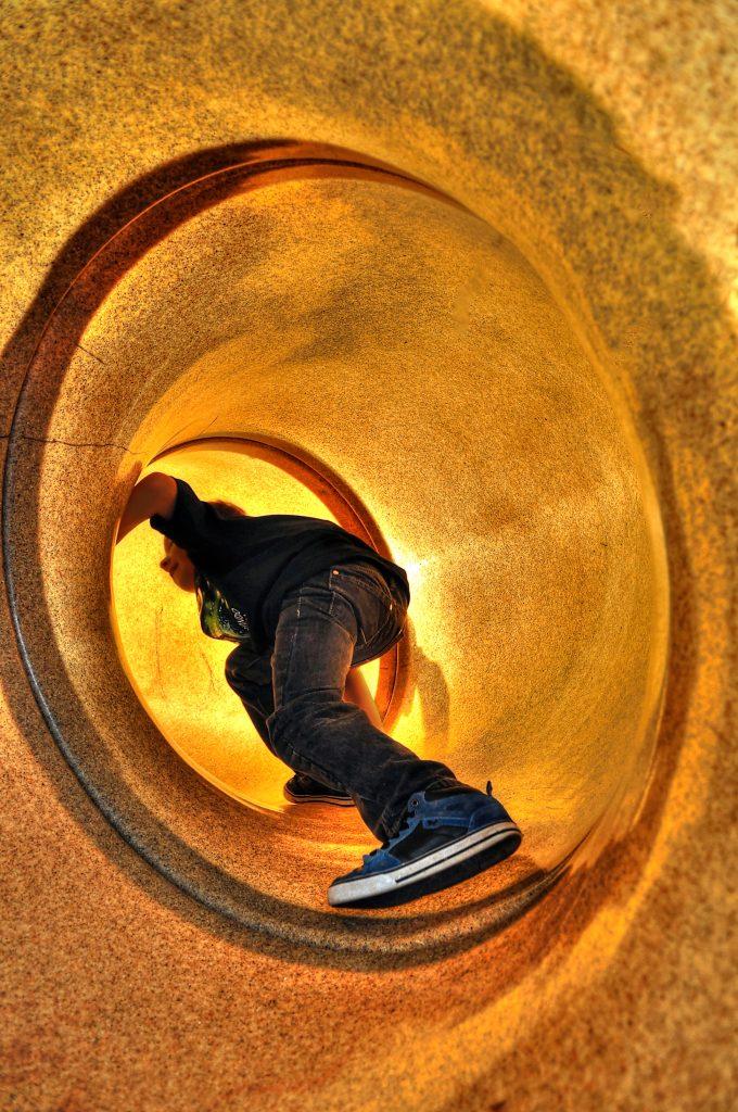 Young boy climbing up a slide.