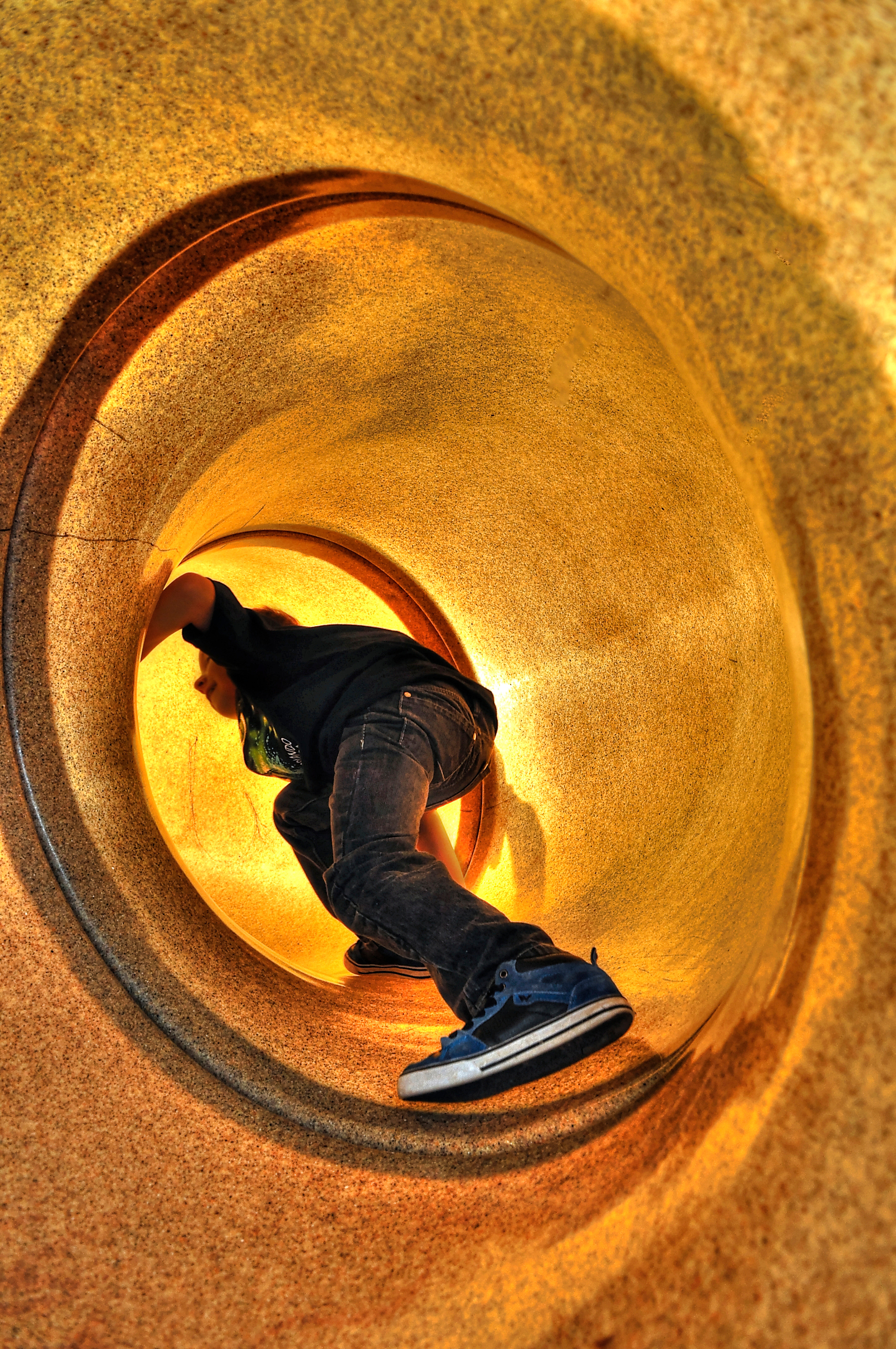 Young boy climbing up a slide.