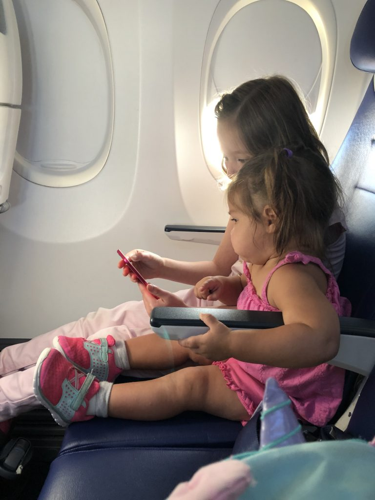Carly and Giabella enjoying sharing a seat on the airplane.